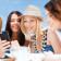 summer holidays, vacation and technology - girls looking at smar