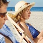 Outdoor beach sand sea water day summer couple young woman man blonde dark haired dark sunglasses