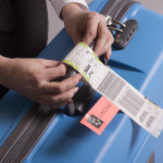 Airline check in luggage tag being attached to a suitcase. Priority tags
